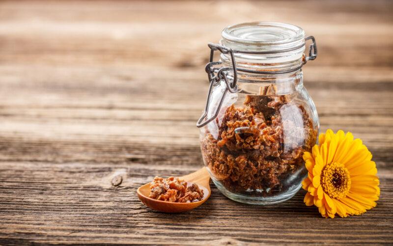 Propolis granule in glass jar on rustic wooden background